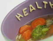 Eating healthy with vegetable soup, noodle letters forming 'health'