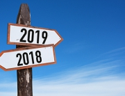 New Year wooden road sign with shining blue sky background