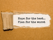 The text Hope for the best Plan for the worst appearing behind torn brown paper