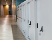 Select focus for key. White Cabinet for document storage. The keys are plugged into the filing cabinet. The filing cabinet is located on the floor beside the walkway.